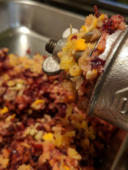 grinding cranberries and oranges